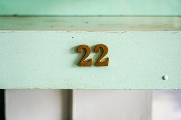 22 number vintage wooden decoration pieces on mint green board.