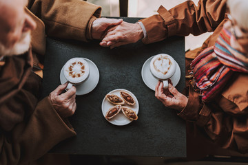 Top view close up picture of old gentleman holding hand of his wife. They sitting at the table with cakes and cups of coffee with latte art
