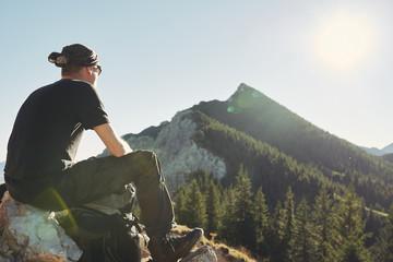 Mann sitzt auf einem BErg Gipfel und schaut auf die Berge, Himmel, Sonne, blau, Freiheit Wall mural