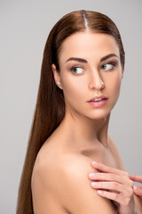 portrait of girl with brunette hair and perfect skin, isolated on grey