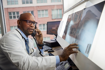 Doctor examining x ray while talking on the phone
