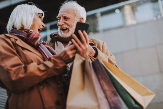 Waist up portrait of cheerful old lady holding cellphone while husband with shopping bags looking at her and laughing