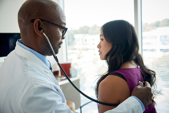 Doctor uses stethoscope on female patient