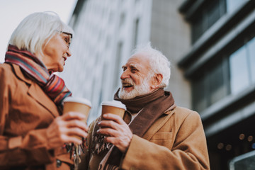 Side view portrait of stylish old gentleman in coat chatting with wife. They holding cups of coffee while looking at each other and smiling