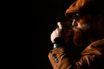 Brutal business man with beard and mustache in brown cap and jacket drink whiskey