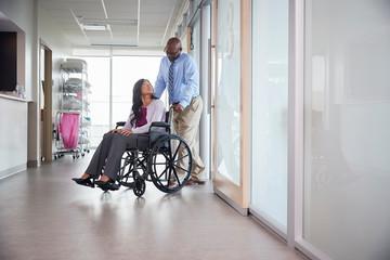 Man pushing a woman in a wheelchair