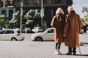 Back view full length portrait of old gentleman with cane and his wife standing on sidewalk. They wearing coats