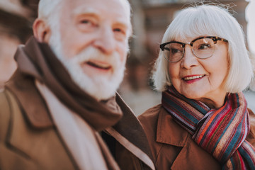Portrait of elderly woman in glasses looking at husband and smiling. Focus on lady