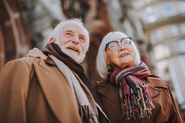 Low angle portrait of senior lady in glasses hugging husband. They looking away and smiling