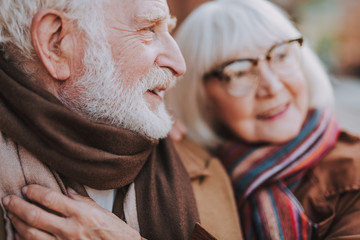 Close up side view portrait of senior bearded man looking away and smiling while lady in glasses standing beside him on blurred background