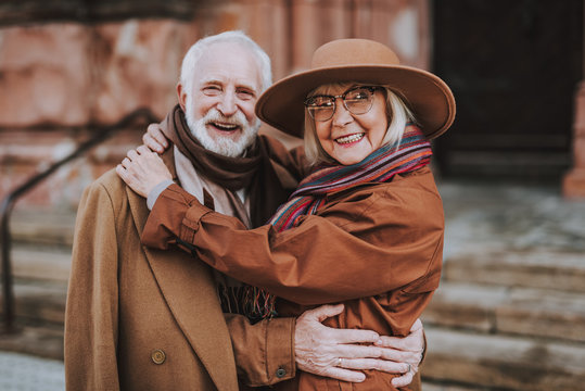 Waist up portrait of stylish bearded man embracing happy wife. They looking at camera and smiling