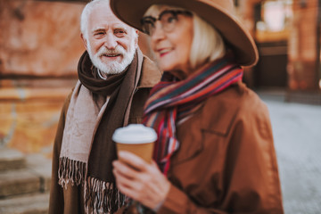 Senior couple. Portrait of smiling elderly gentleman looking at wife while she holding cup of coffee. Focus on man