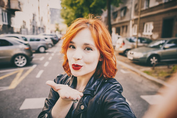 portrait of fashionable young woman wearing a leather jacket taking selfie with smartphone