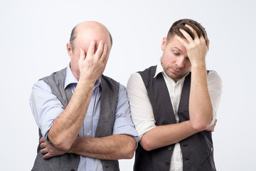 Two mature men with face palm gesture. Wall mural