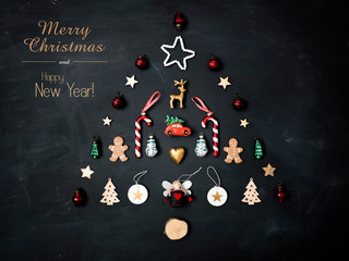merry christmas lettering and christmas tree shaped out of different Christmas deco items, on black chalkboard