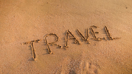 Closeup photo of word Travel written on wet beach sand. Concept of tourism, traveling, trips and journeys.