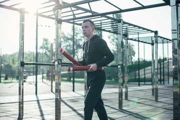Calm man in sports clothes holding two boxing sticks