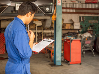 handsome asia man automotive mechanc in garage with copy space