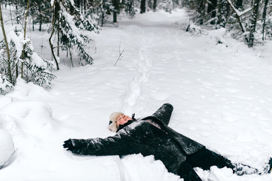 woman lies on snow and makes hands of an angel