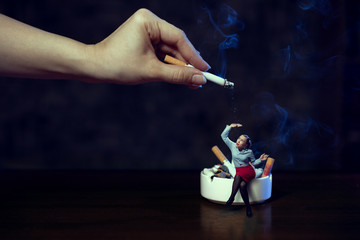 A young woman in an office blouse and a red pencil skirt smokes while sitting on an ash-tray; on top of her hand shakes off the ashes from a cigarette. Smoking is harmful to health. No Smoking Day.