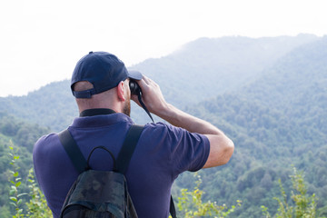 Young man watching with binoculars the birds on top of the mountain against a mountain landscape. Bird watching. Ornithology