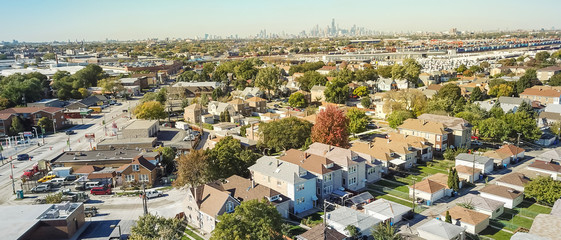 Panorama aerial view traditional residential neighborhood west of Chicago. Row of classic house with garden and detached garage. Skylines from downtown in background
