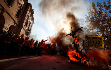 A fireman raises up a flare during a protest against cuts and working conditions in front of Catalonia Parliament in Barcelona