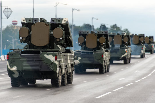 column of military vehicles traveling on road on left side