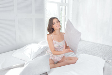 Young girl in nightgown in the morning in the bedroom on the bed