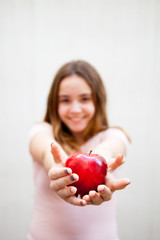Teenage girl holds a red apple with her hands and offers it
