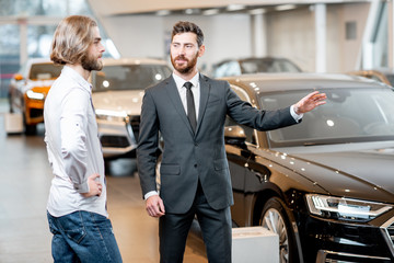 Professional car salesman talking with male client showing new cars at the showroom