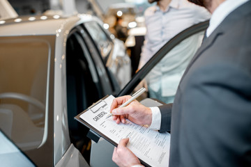 Manager filling car rental documents standing in the showroom with car on the background