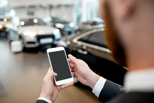 Businessman holding phone with empty screen to copy space in the showroom with cars on the background