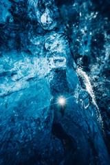 Traveler walking in blue ice cave