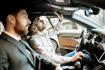 Young man trying new car sitting with salesperson in the luxury car interior at the showroom