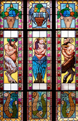 Colorful stained glass window with bowls and fauns.