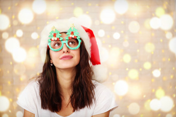 Beautiful young woman wearing santa claus furry hat & masquerade glasses for Chritmas celebration event. Attractive female being silly, making faces at dress up party. Background, close up, copy space