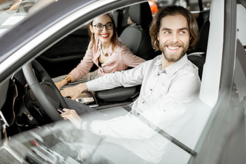 Young happy couple choosing a new car sitting inside in the showroom
