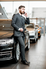 Elegant businessman or salesperson in the suit talking with phone in the car showroom