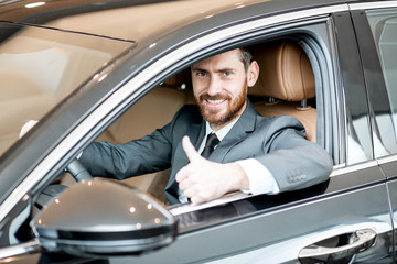 Portrait of an elegant businessman sitting on the driver seat in the luxury car at the showroom