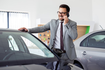 Businessman having a phone call at the car showroom