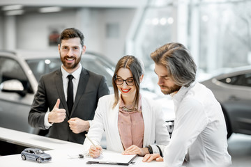 Business couple signing some documents at the stand with happy salesperson on the background in the showroom