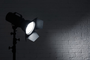 Professional photo studio lighting equipment near brick wall. Space for text