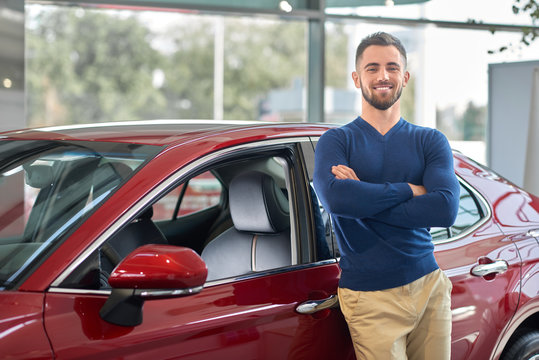 Young attractive driver smiling near his new vehicle.