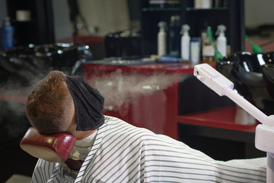Man lying on chair in barber shop while steam blowing