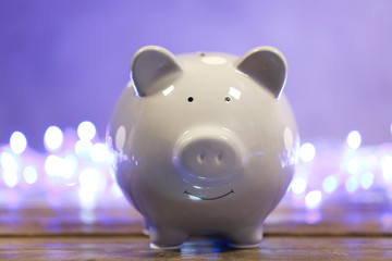 Cute piggy bank on table against blurred Christmas lights