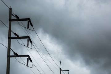 Electricity pole and high voltage power lines on the road with cloud and overcast sky