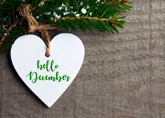 Hello December.Decorative white wooden Christmas heart and fir tree branch on old wooden background.Winter holidays concept with space for text.Selective focus.