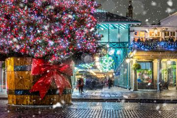 Weihnachtliches London im Bezirk Covent Garden mit Weihnachtsbaum und Schneefall bei Nacht