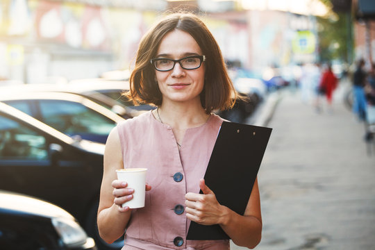 business  woman holding a cup of coffee and files going to work
